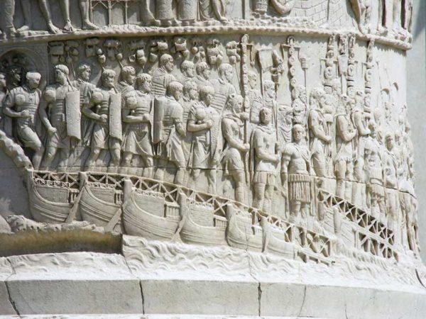 Particolare dalla Colonna traiana: l'esercito romano passa il Danubio su un ponte di barche, dando inizio alla prima campagna in Dacia (101-102 d.C.). La disposizione delle figure e la cura dei particolari consentono di cogliere l'ordine e la disciplina con i quali i diversi reparti si accingono alla guerra.