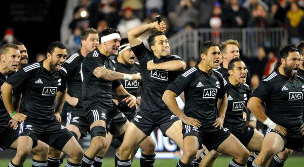 Giocatori della squadra di rugby degli All Blacks mentre mimano la celebre Haka, danza rituale maori: spalancano gli occhi, digrignano i denti, mostrano la lingua, si battono violentemente il petto e gli avambracci, esprimendo così potenza e coraggio, elementi propri dello spirito guerriero dei Maori.